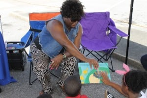 A staff member from the Jacksonville Public Library reads to kids at the 2014 Jacksonville Baby Buggy Walk in the Park at the Magnolia Project